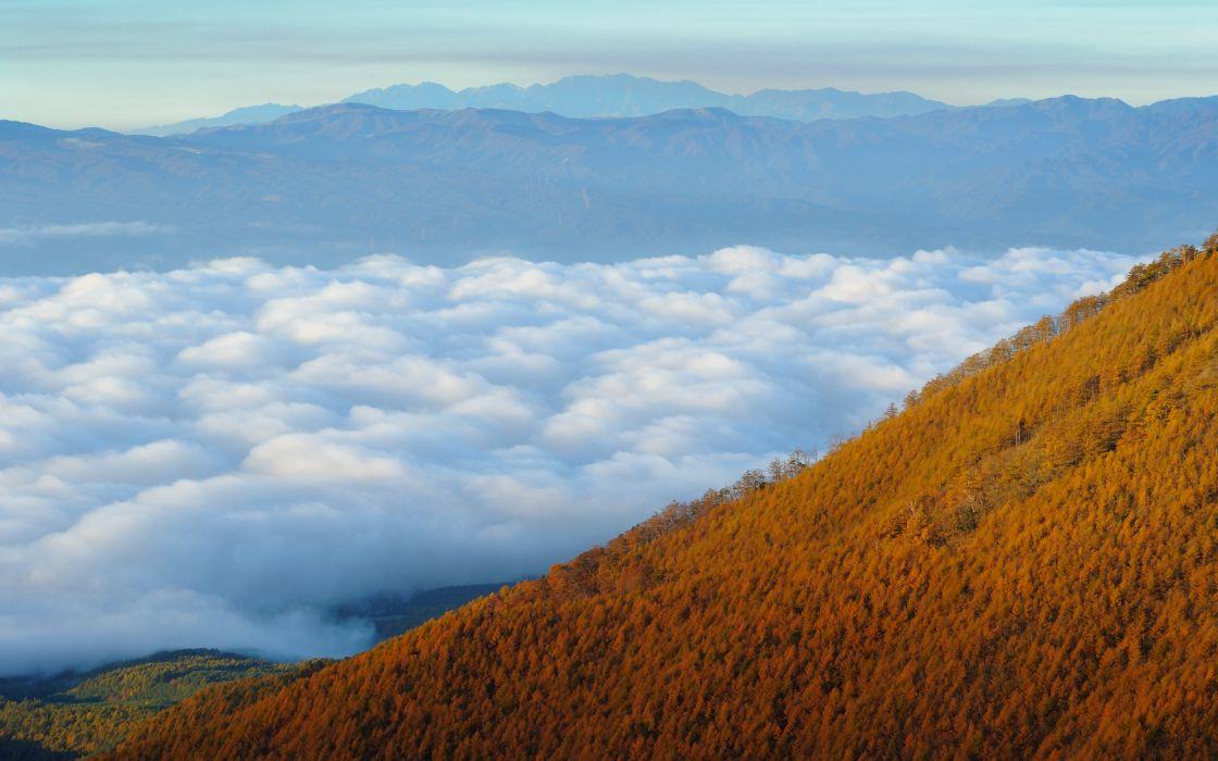 Mountain between clouds wallpaper