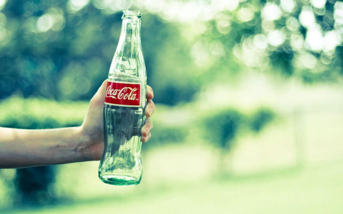A coca-cola in one hand wallpaper