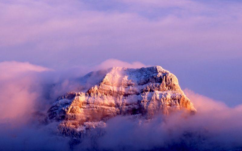 Snowy peak in the clouds wallpaper