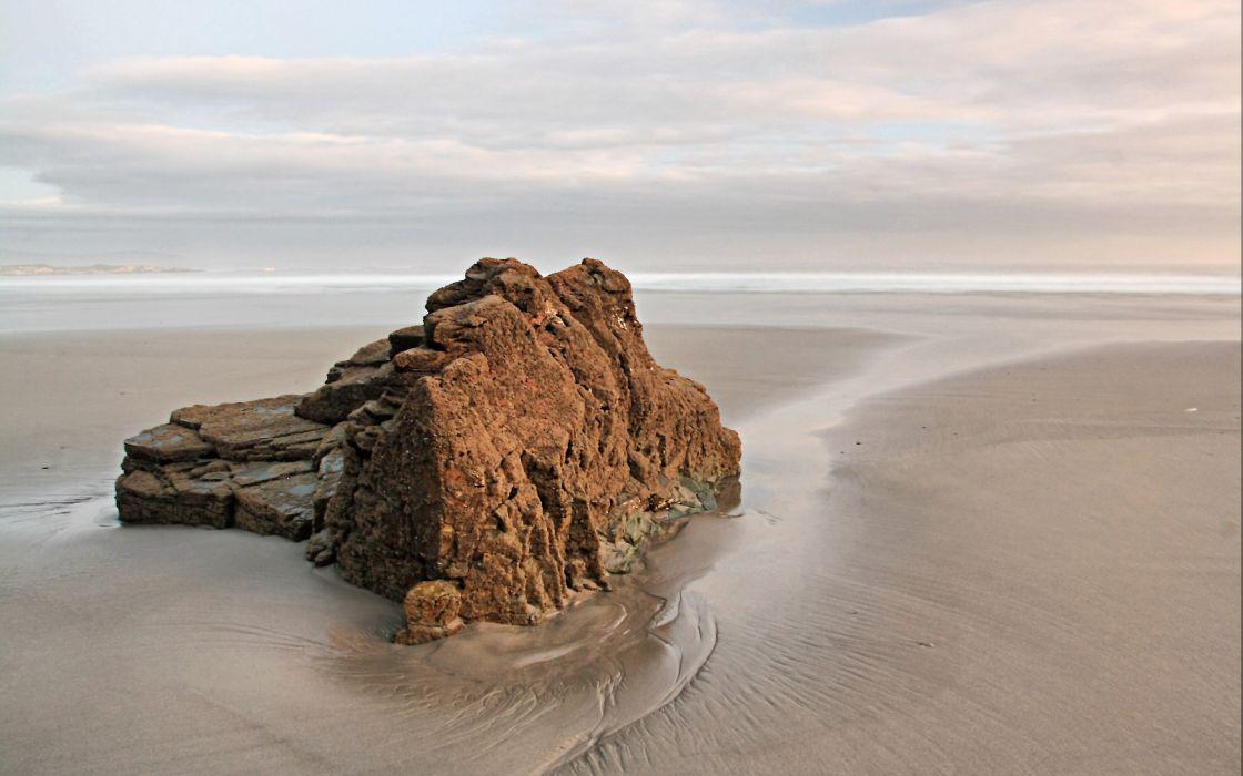 A rock in the beach wallpaper