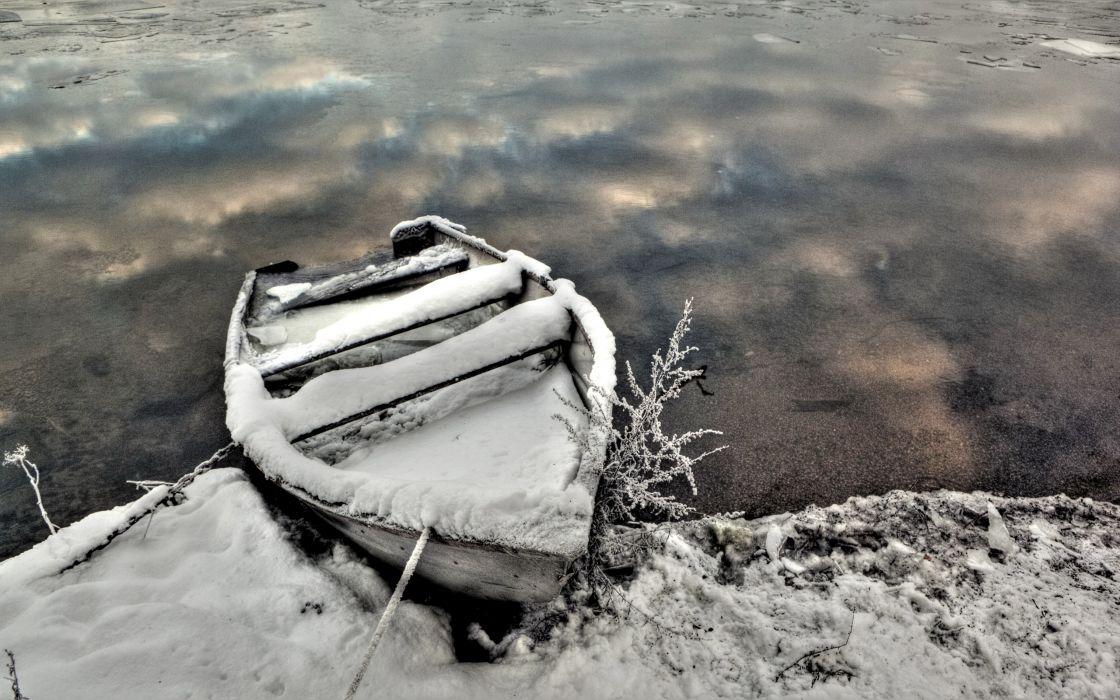 Snowy boat in the frozen lake wallpaper