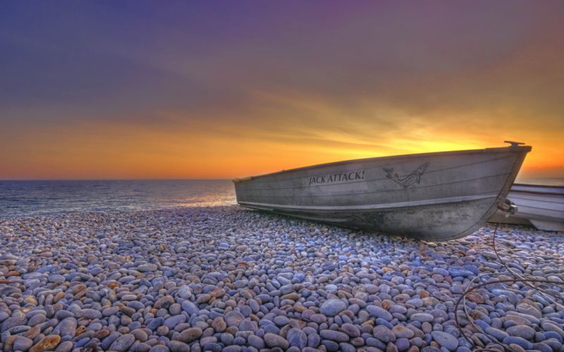 Boat over a pebbles beach wallpaper