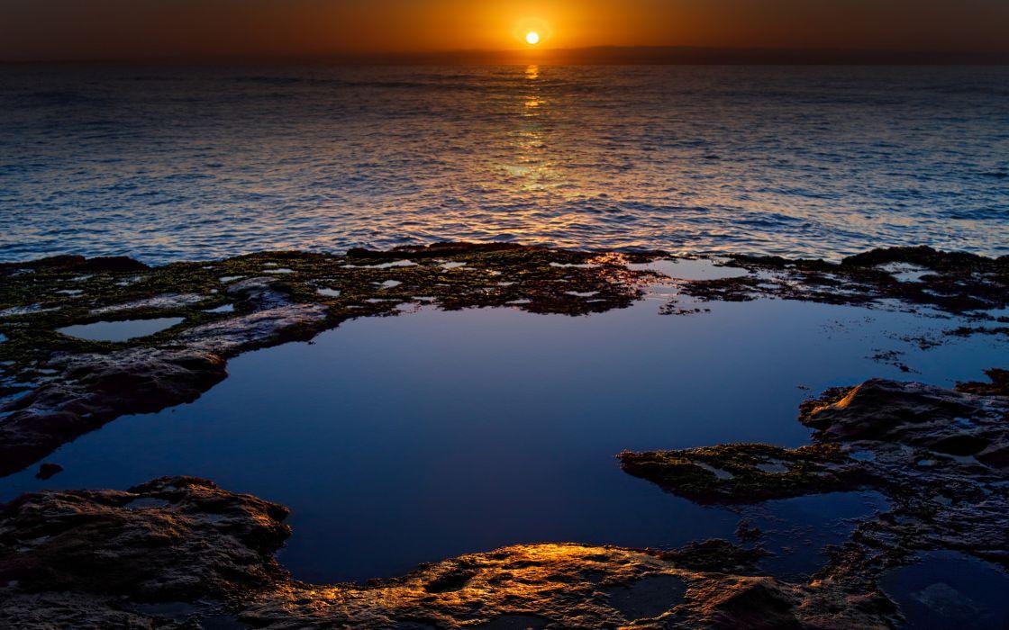 Rocks in the ocean at sunset wallpaper