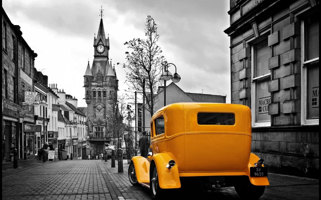 Vintage yellow car in a gray city wallpaper