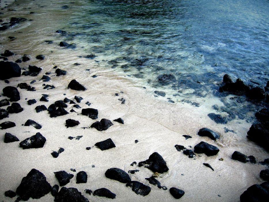 Black rocks on white sand beach wallpaper