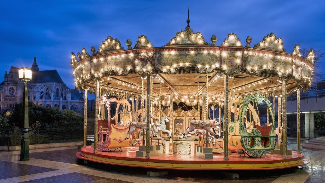 paris france church carousel amusement night lights animals horses children fun rides sky clouds architecture buildings church lamp post wallpaper