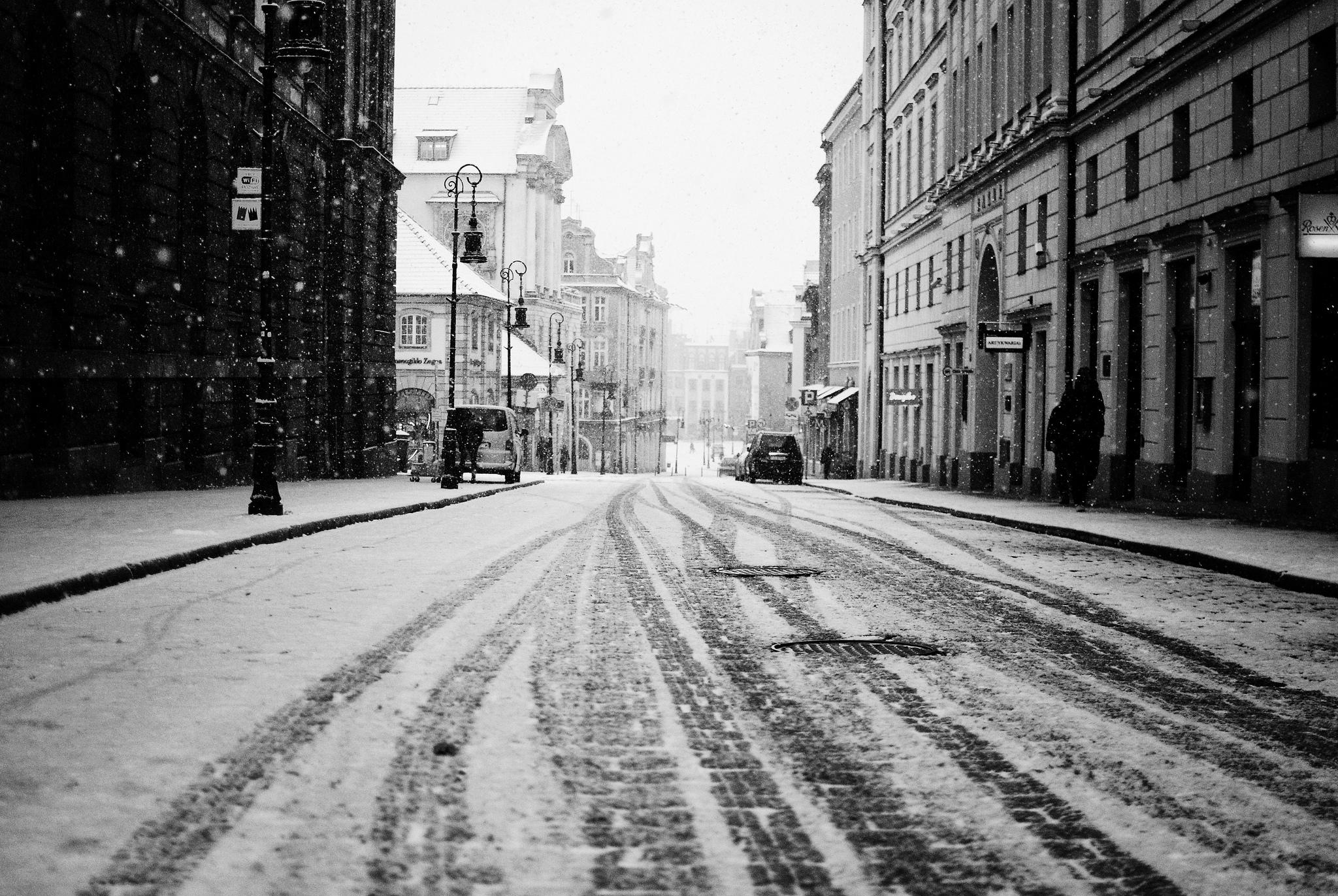 City road snow street buildings houses people cars tracks ...