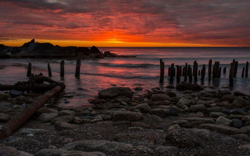 Sunset Ocean Posts Rocks Stones Beach wallpaper