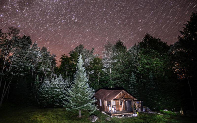 Cabin Night Forest Trees Stars Timelapse wallpaper