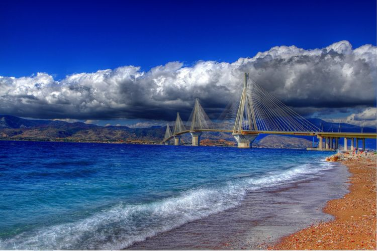 Greece Gulf of Corinth cable-stayed bridge Rio Antirio water coast color stones pebbles sky clouds wallpaper