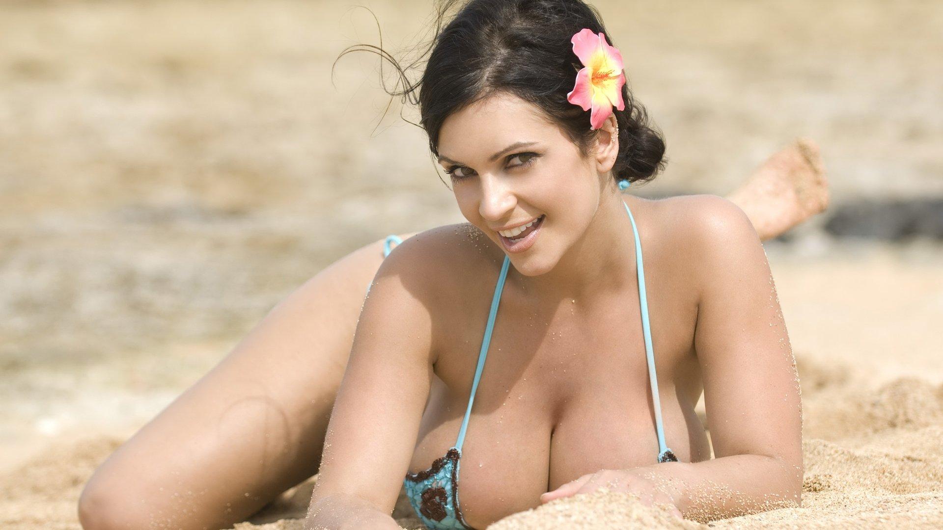 девушки на пляже с большой грудью намазывает свои