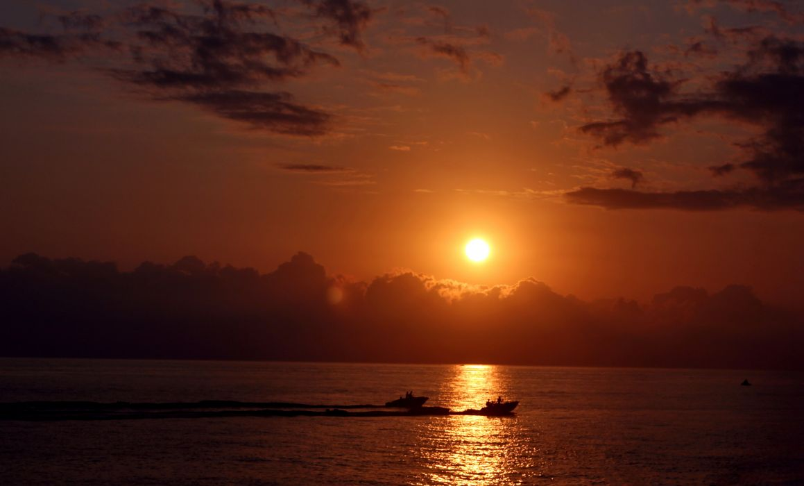 sunset glowing water reflection sun boats wallpaper