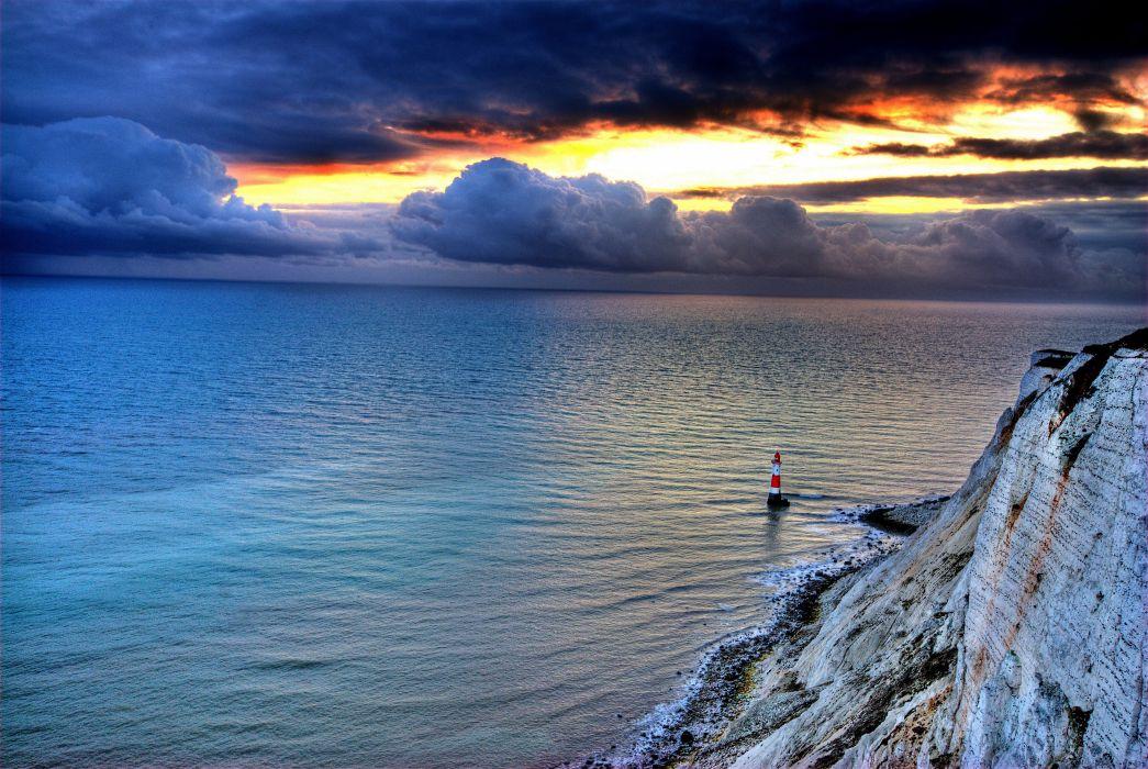 Sea rocks lighthouse sky clouds sunset glow nature landscape ocean wallpaper