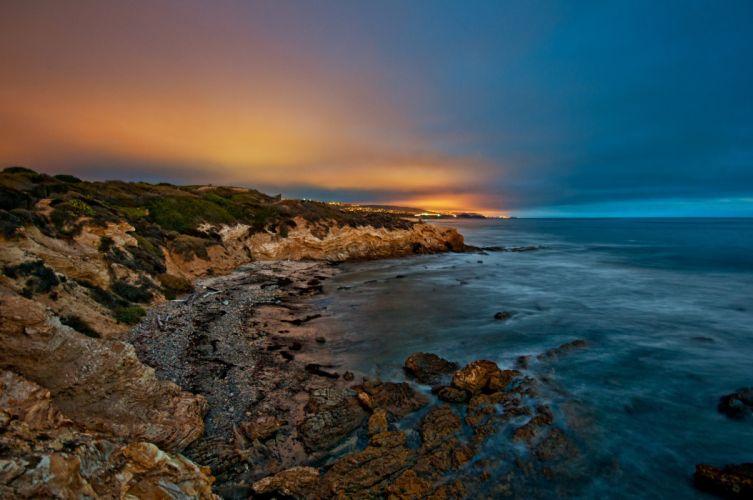 sea beach stones evening dusk lights sunset ocean wallpaper