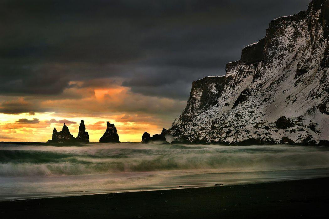 sky clouds glow rocks shore sea waves storm wallpaper