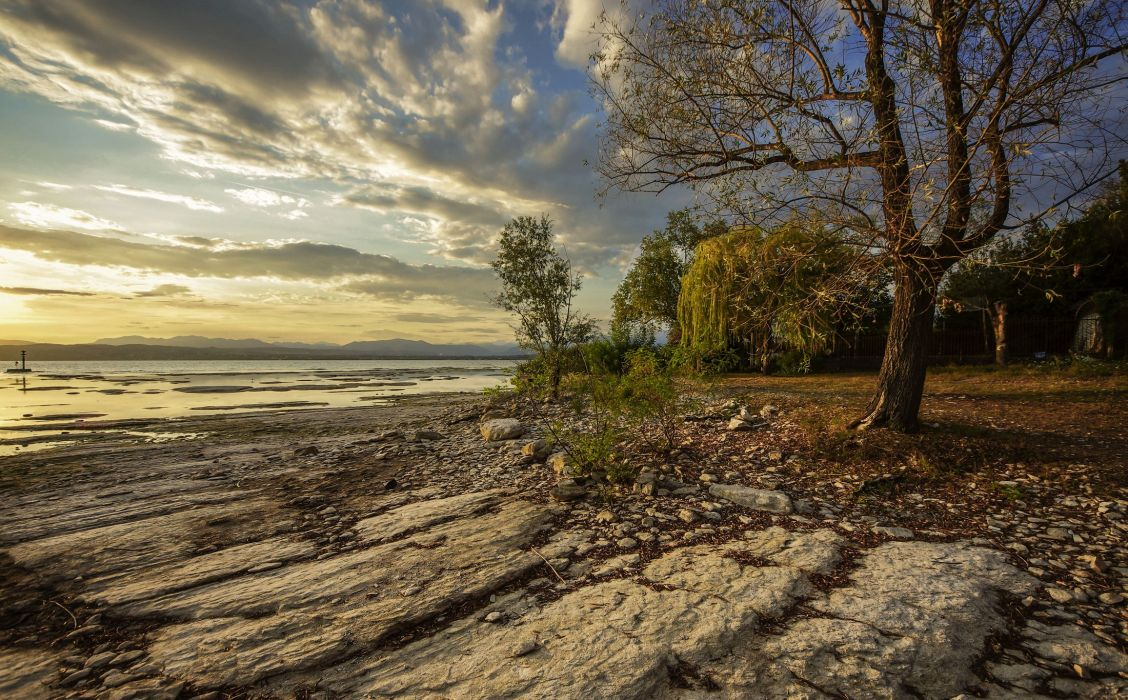 Italy Coast Sunrises and sunsets Stones Scenery Clouds Trees Sirmione Lombardy Nature wallpaper