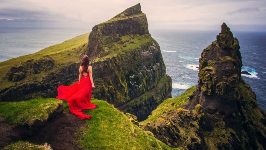 a-girl-in-red-dress-standing-on-high-mountain-and-looking-at-the-sea wallpaper