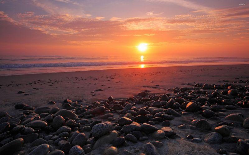 Sunset over ocean water sand rock sky beaches wallpaper