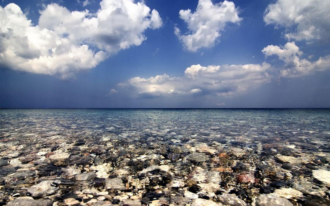 sea water transparent stones bottom clouds sky wallpaper