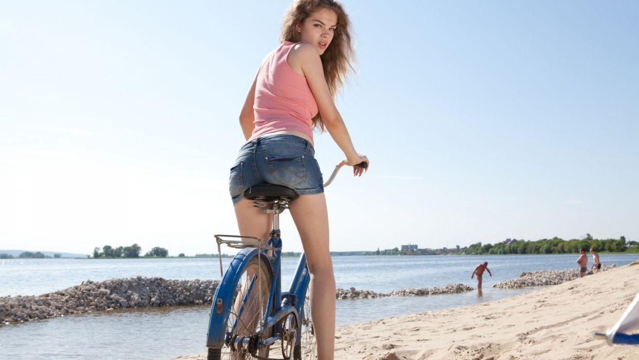 Sensuality woman-girl-sexy-sensual-shorts-denim-bike-beach-sand wallpaper