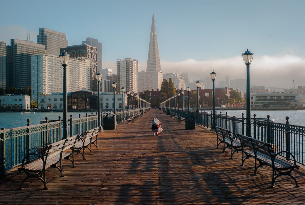 bay bench boardwalk bridge buildings city cloud district downtown fog lampposts lamps man ocean people roadway san francisco scenery sea sky sunny tower town view water wood bridge wooden wallpaper