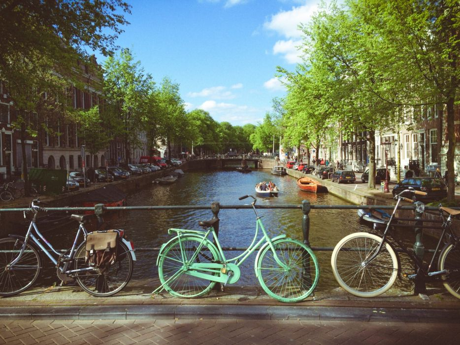 bicycles bike boats bridge buildings canal city cycle cyclist downtown outdoors parked cars pavement river road street summer tourism town transportation system travel trees urban water wheel wood wallpaper