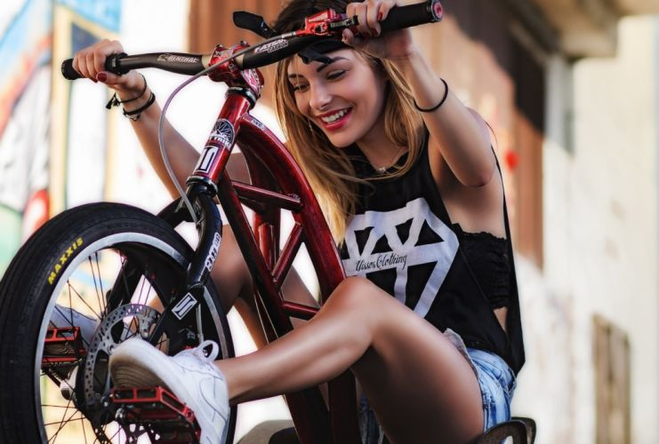 Photography-bicycle-sensuality-sensual-sexy-woman-girl-shorts-jeans-denim-torn-model-smiling-sneakers wallpaper