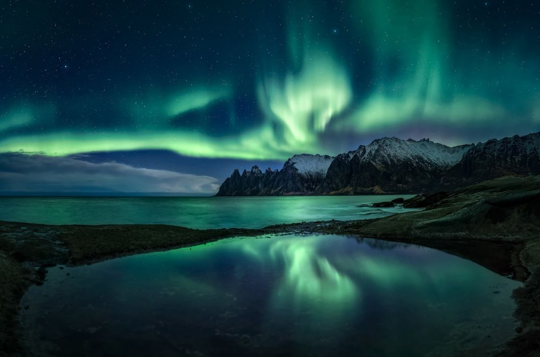 Northern lights in the starry sky above the mountain lake wallpaper