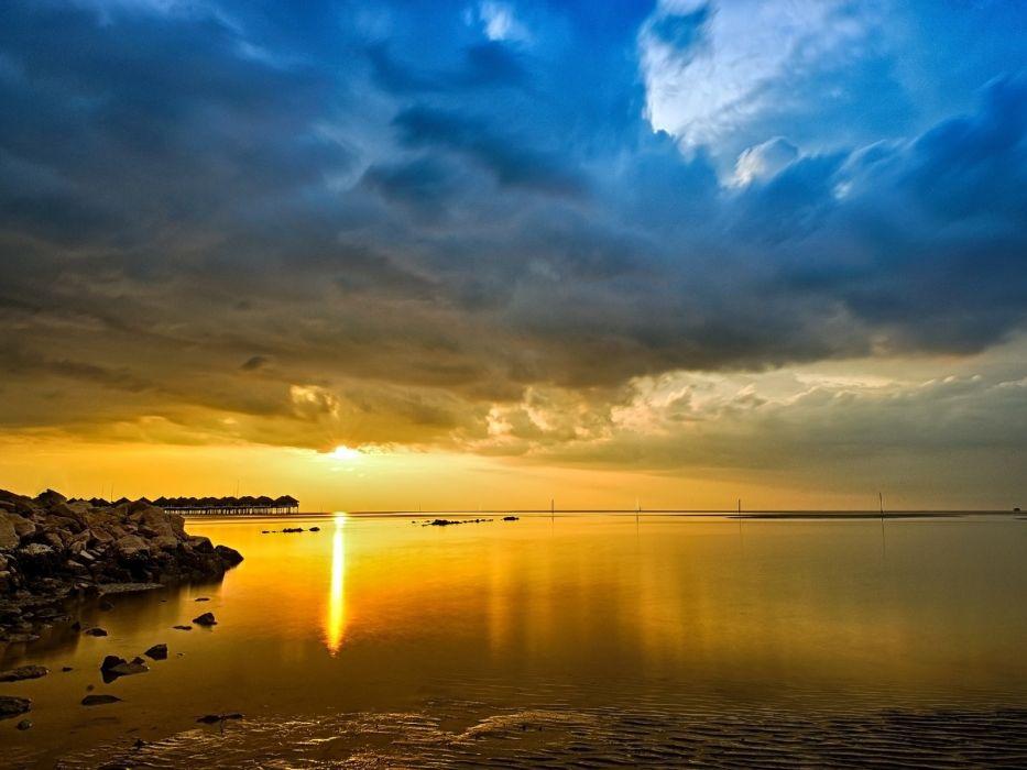 Sea sky clouds sunset stones shore horizon bungalows wallpaper