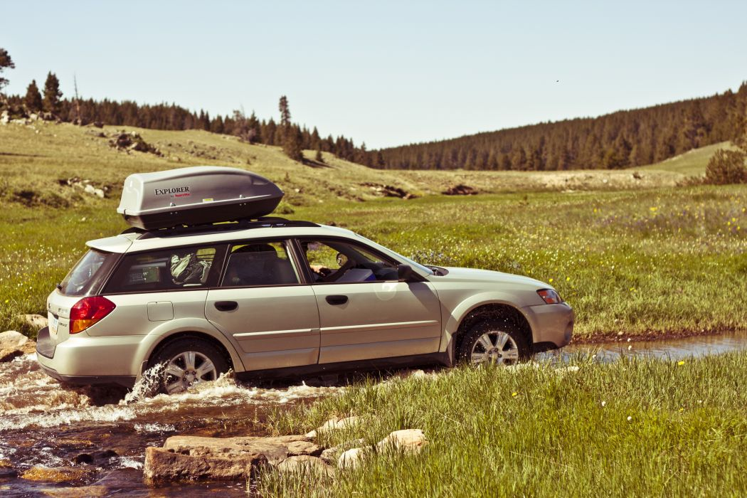 automobile automotive camping car daytime grass rocks station wagon travel trees vehicle water wallpaper