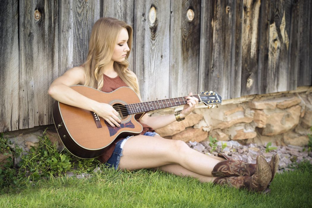 Woman in Brown Tank Top With Acoustic Guitar Sitting on Green Grass Beside Brown Wooden Fence wallpaper