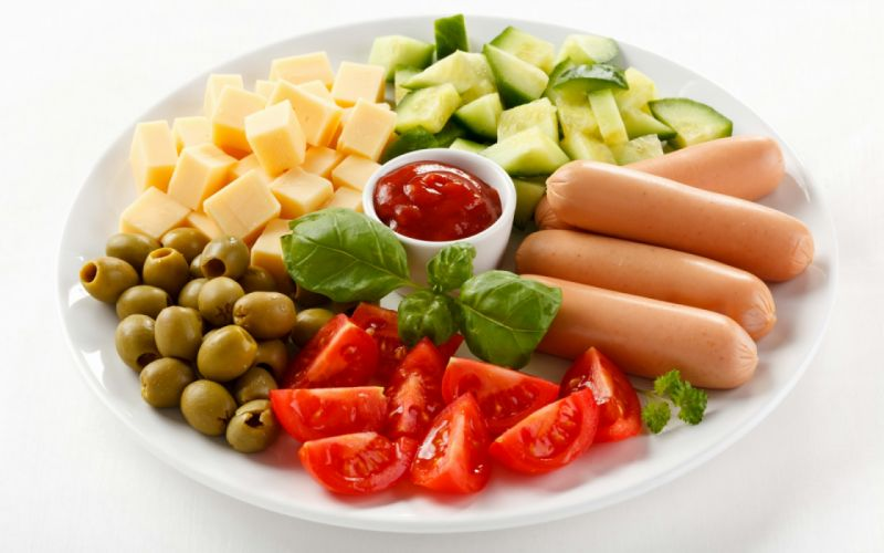 On a round plate are sausages and sliced tomatoes cucumbers cheese as well as olives and red sauce wallpaper