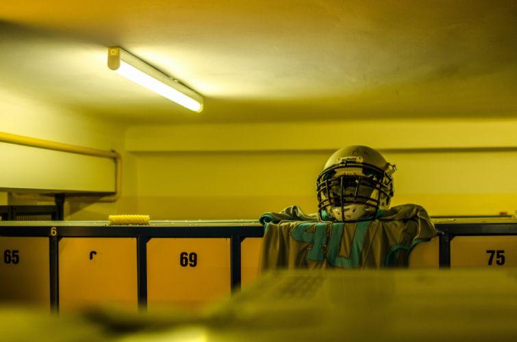 American football blur changing room empty helmet indoors light locker room lockers numbers room seat sport uniform wallpaper