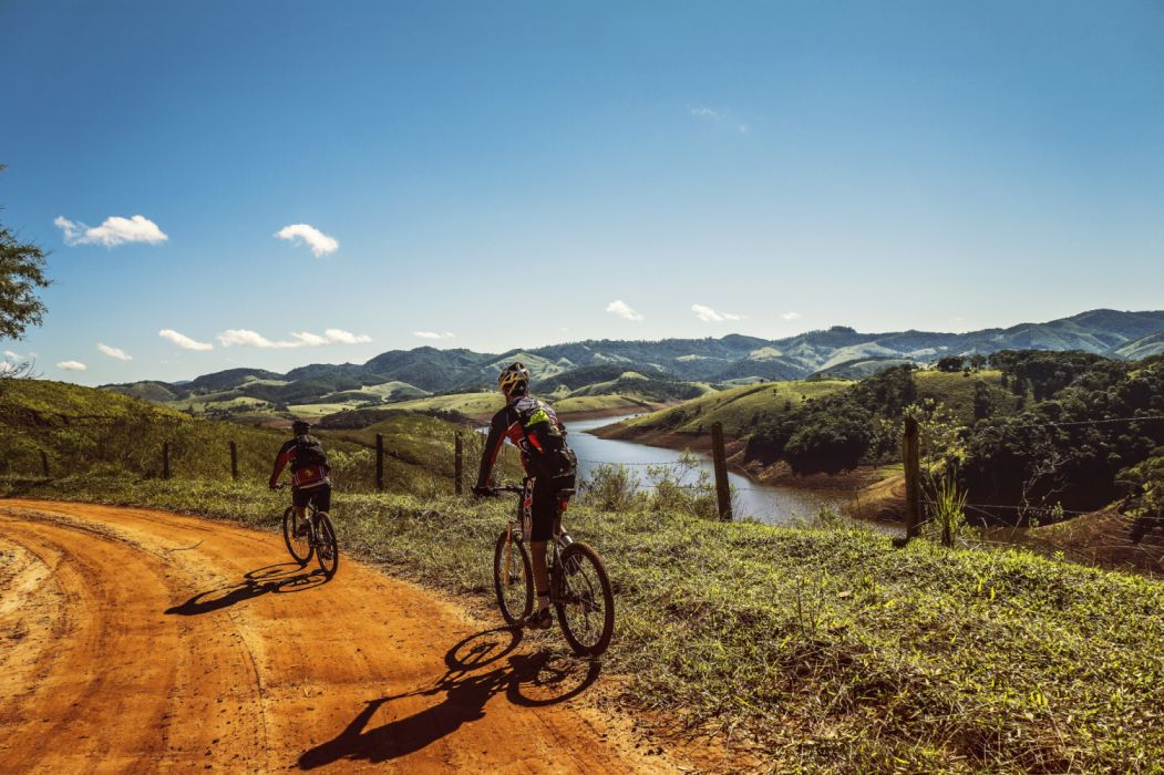 Bicyclist Passing the Road Near the River wallpaper