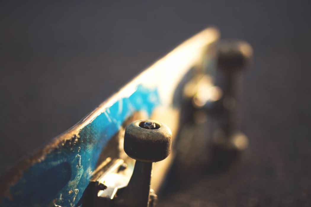 Blue and White Skateboard on Concrete Floor Slightly Tilted wallpaper