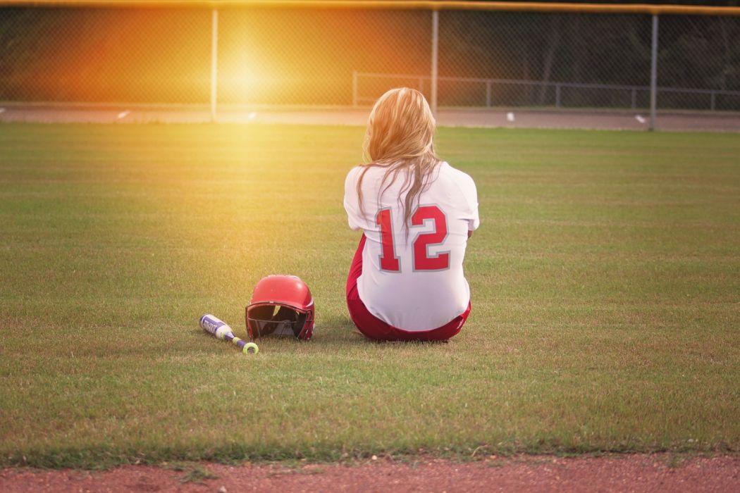 Female Baseball Player Sitting on Grass Field Beside Helmet and Baseball Bat wallpaper