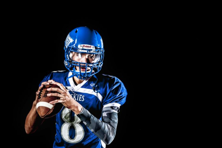 Man Holding Football and Football Uniform in Black Background wallpaper