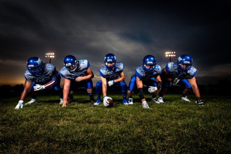 Football Players in Blue Jersey Lined Under Grey White Cloudy Sky during Sunset wallpaper