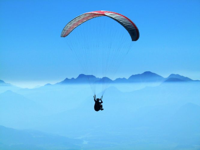 Person Doing Paragliding Above Clouds during Daytime wallpaper