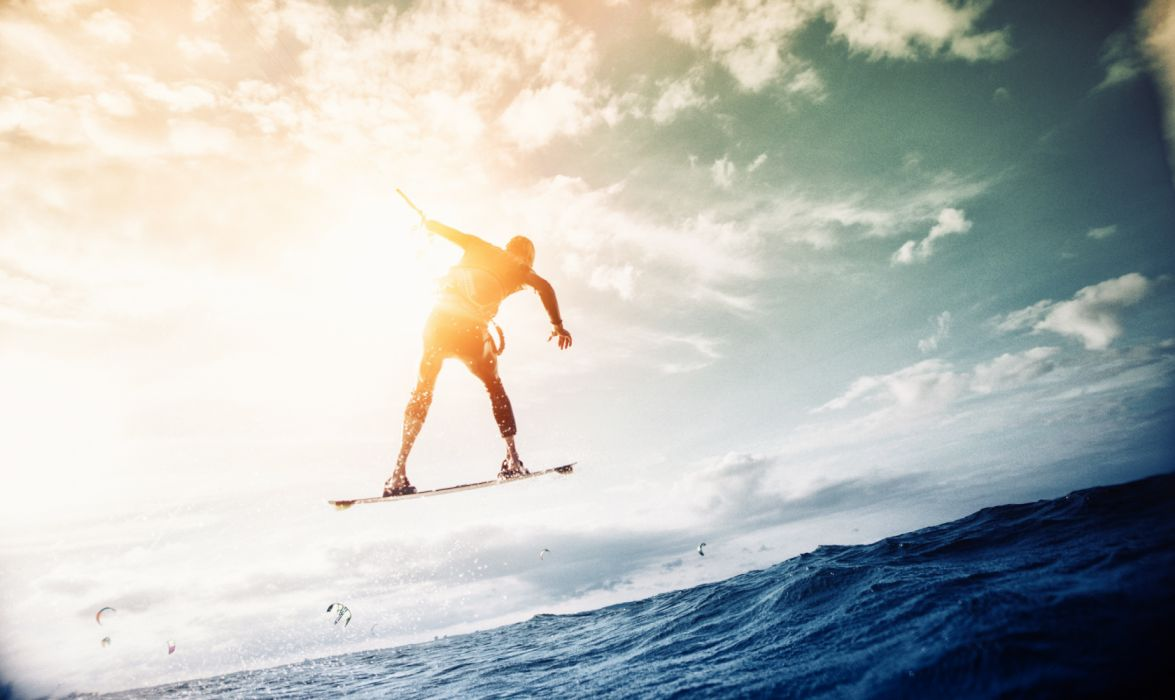 Man Wakeboarding over Body of Water wallpaper