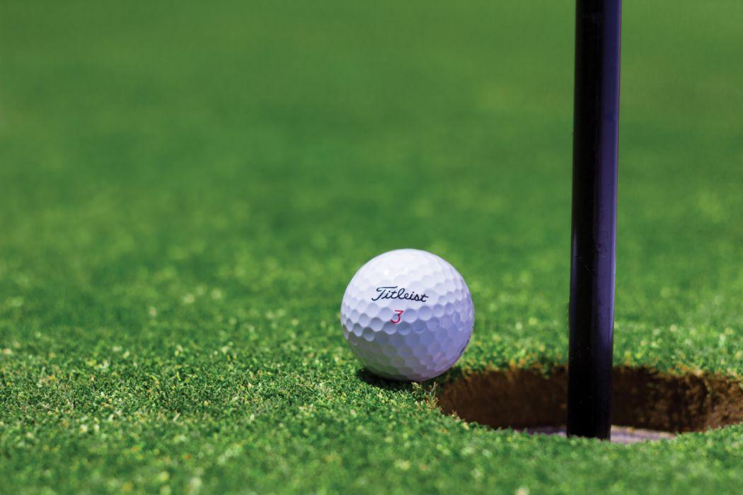 Titrist Golf Ball Near Golf Hole wallpaper