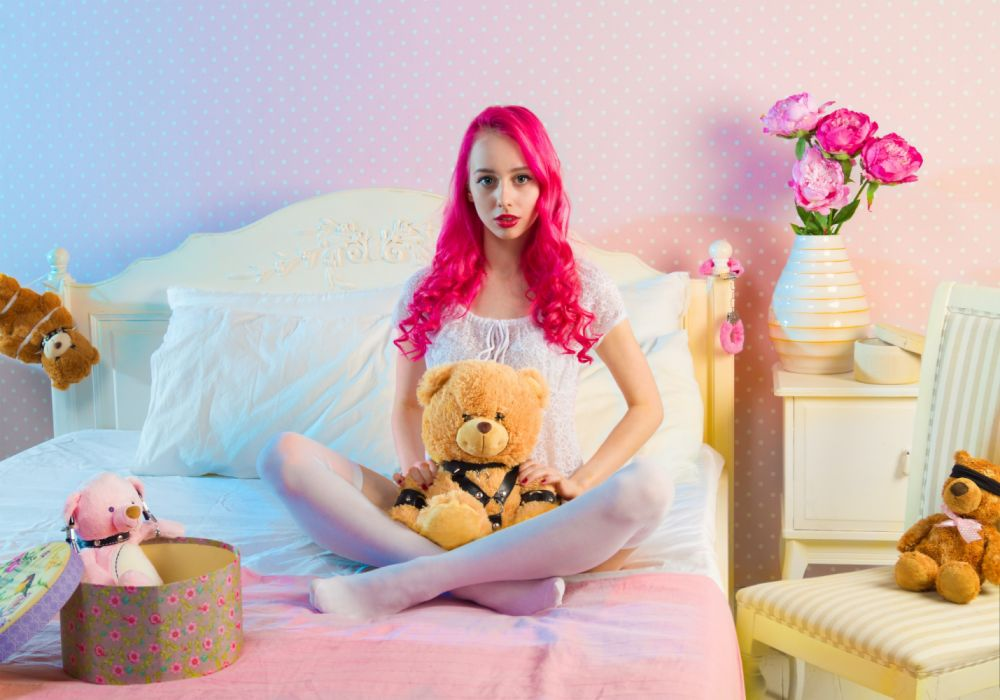 Pink Long Haired Woman Sitting on Double Bed With Bear Plsuh Toy at Daylight wallpaper