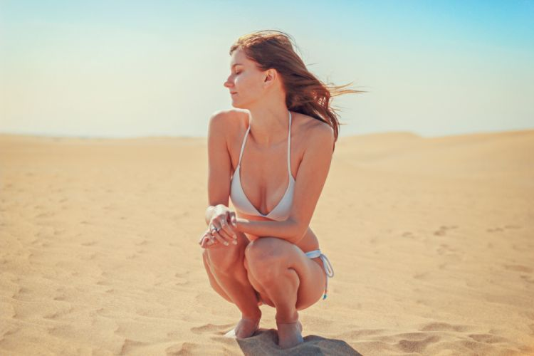 Young Woman Sitting on Sand at Beach wallpaper