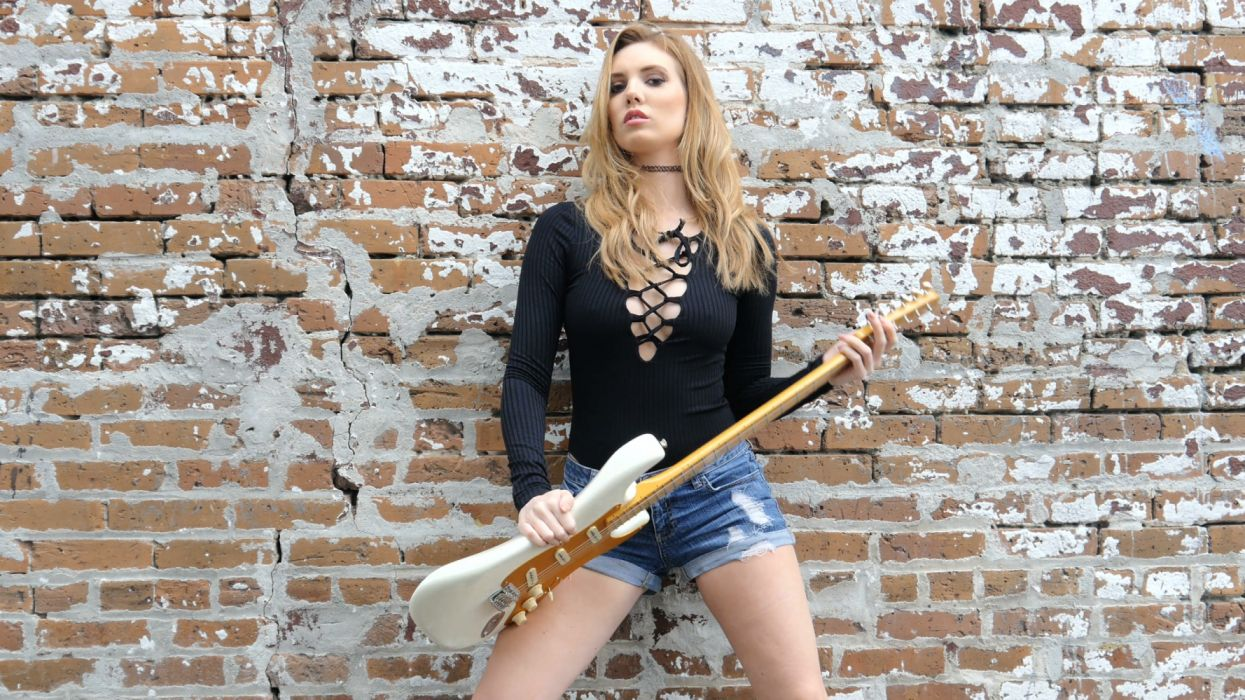 Sexy hipster girl with electric guitar on grunge wall background wallpaper