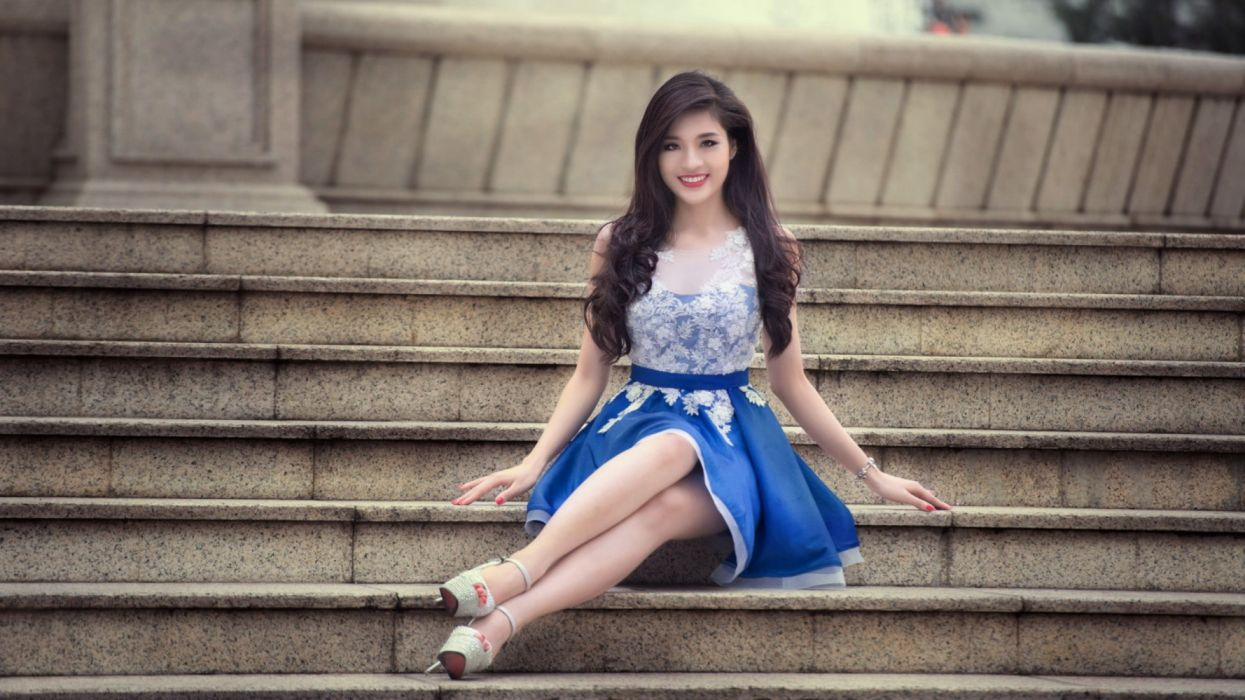 woman in white and blue floral sleeveless dress sitting on concrete stairs wallpaper